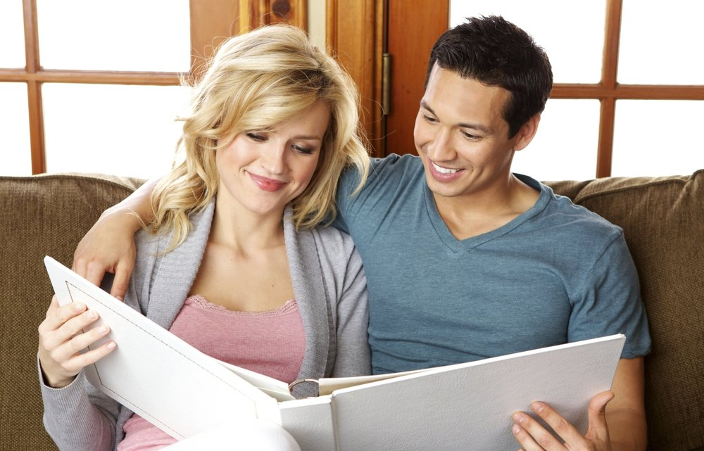 Diverse Couple looking at a Wedding Album Smiling