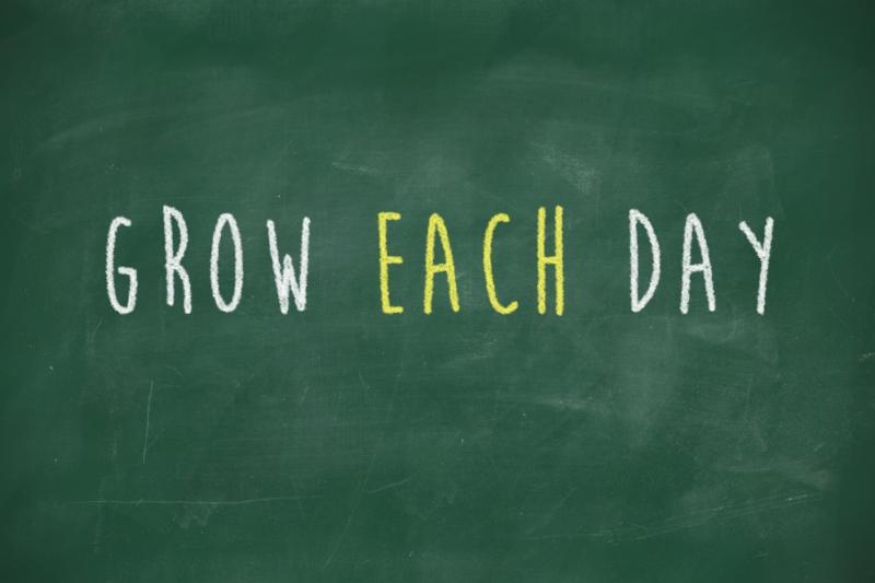 Grow each day handwritten on blackboard