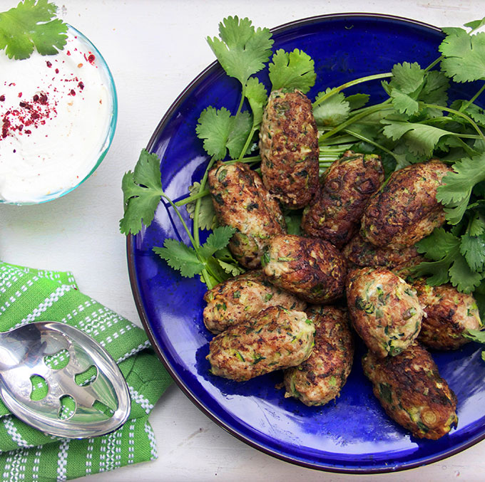 Turkey Zucchini Meatballs with Lemony Yogurt Sauce   Healthy, delicious turkey meatballs from chef Yotam Ottolenghi  Author: Panning The Globe, adapted from cookbook entitled Jerusalem   Recipe type: Appetizer or Main Course  Cuisine: Israeli  Serves: 6-8        Ingredients   Yogurt Sauce   ½ cup sour cream *  ⅔ cup lowfat plain Greek Yogurt  1 tablespoon lemon juice  1 small garlic clove, pressed or finely minced  1½ tablespoons olive oil  1 tablespoon sumac  ½ teaspoon salt  ¼ teaspoon fresh ground black pepper   Meatballs   1 pound ground turkey (white or dark meat)  1 large egg  1 large zucchini, grated  6 scallions, sliced thin  2 tablespoons chopped mint leaves  2 tablespoons chopped cilantro leaves  2 large cloves garlic, pressed or finely minced  1 teaspoon ground cumin  1 teaspoon salt  ½ teaspoon cayenne pepper  ½ teaspoon fresh ground black pepper  Vegetable oil for sautéing  * For a lower fat sauce you can swap out the sour cream for low fat yogurt. The taste is a bit more tart but still delicious.  Instructions   Make the Sauce  Combine all ingredients. Set aside or refrigerate for up to 3 days, until needed.   Meatballs  Preheat oven to 425F. Line a baking sheet with parchment paper. In a large bowl combine turkey, zucchini, scallions, egg, mint, cilantro, garlic and spices. Using your hands, shape the meatballs (about 2½ tablespoons per ball) by gently squeezing them and tossing them from hand to hand. Set formed meatballs on a large plate. (makes about 18)  Heat 2 tablespoons oil over medium heat in a large skillet. Slice half the meatballs into the pan and brown them on all sides, about 4 minutes. Carefully transfer them to the baking sheet. Repeat with the rest of the meatballs, adding extra oil to the pan, if needed. Slide the tray into the center of the oven and cook for 6-7 minutes, until cooked through. Serve with lemony yogurt sauce.