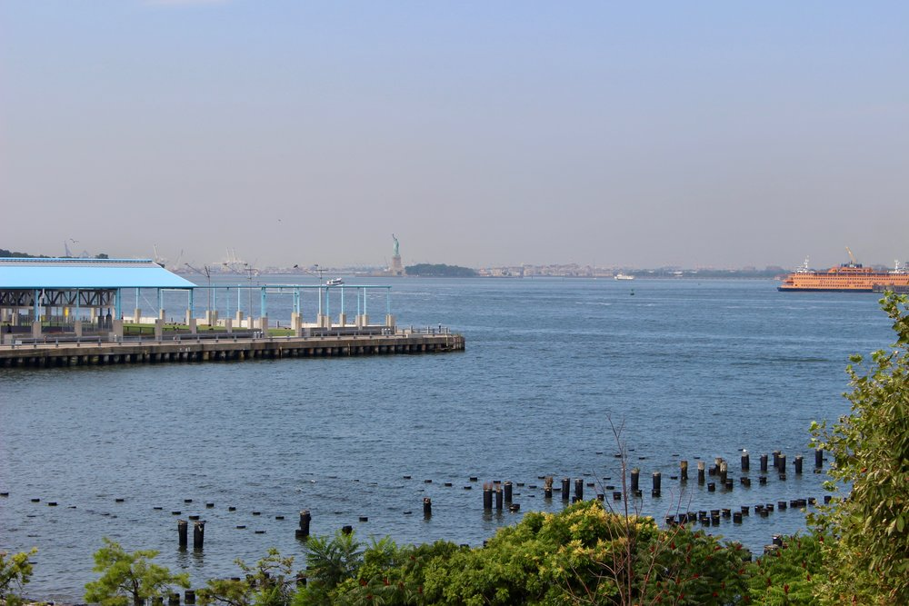 "Reaching the end of the footbridge and stepping out onto the path, here is the view.  Note the Staten Island Ferry making its way into the Harbor and the Statue of Liberty.  It is always breath taking, no matter how many times you approach this ""vista."""