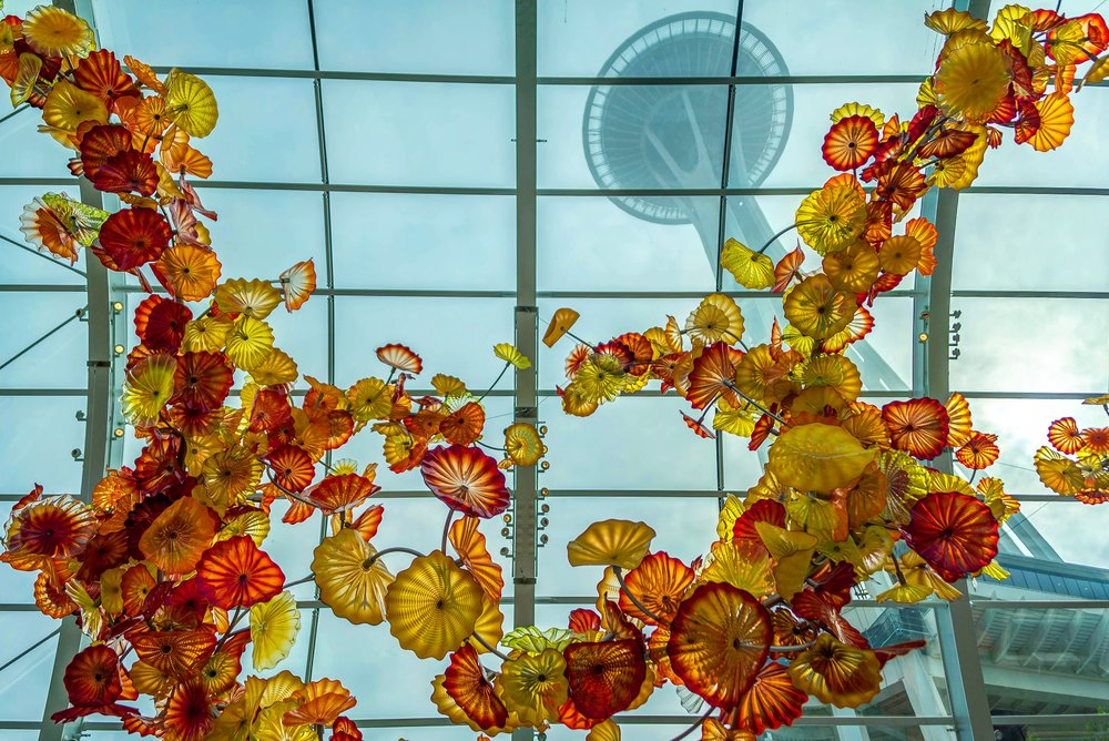 "the Space Needle towering the ""Glasshouse"" at Chihuly Garden and Glass"