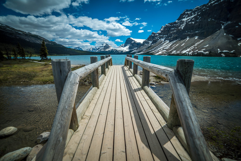a wooden bridge that leads to Bow Lake