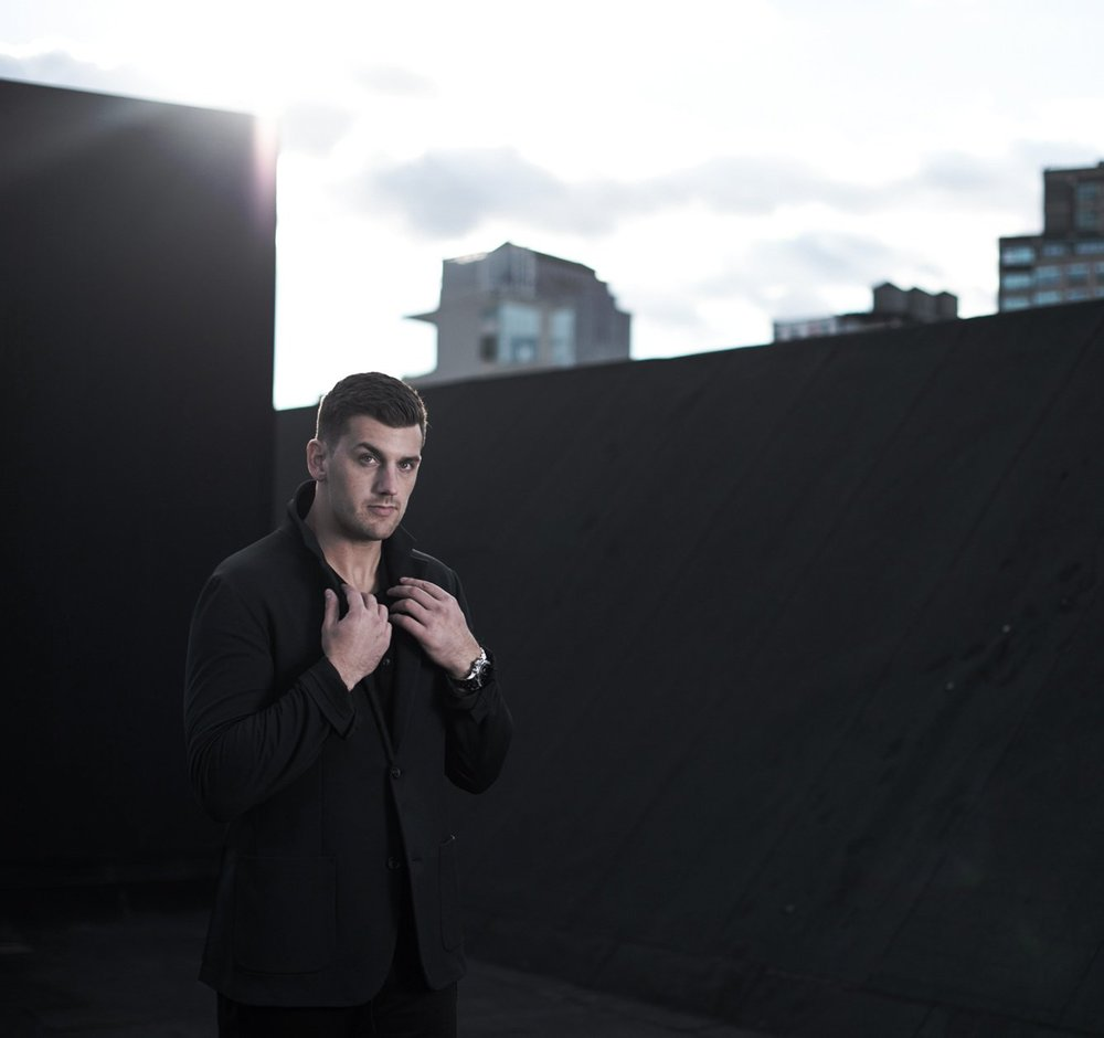 Steve Maneri on a New York City rooftop wearing The Casual Jacket in Black, paired with The Casual Pants in Black and The Long-Sleeve Henley Tee Shirt in Black Italian Rib-Knit.