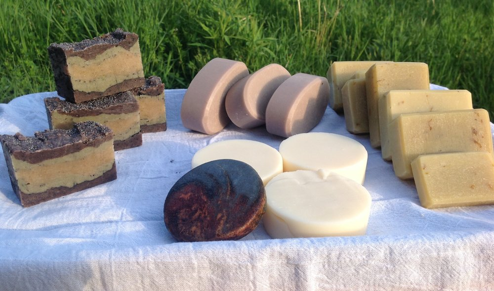 A small sampling of our all natural handmade soaps- left to right: rustic gardener, lavender (back), cedarwood lemongrass (front white), campfire soap (front dark), dandelion calendula bastille.