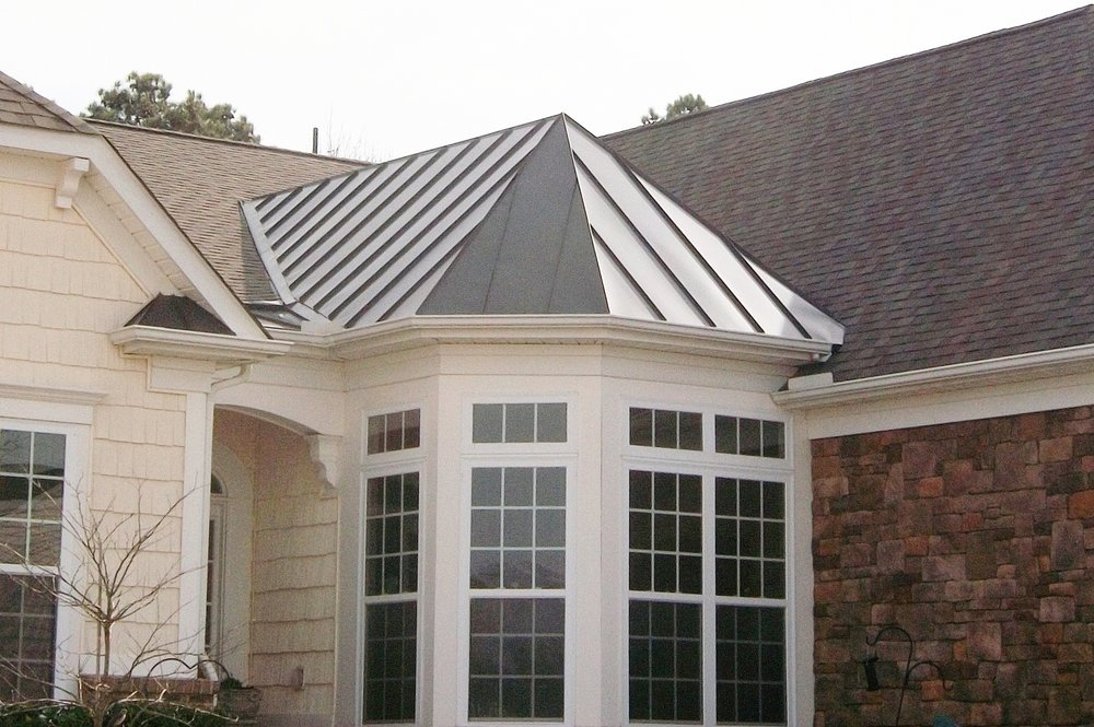 Metal roof material with asphalt shingle roofing on a home
