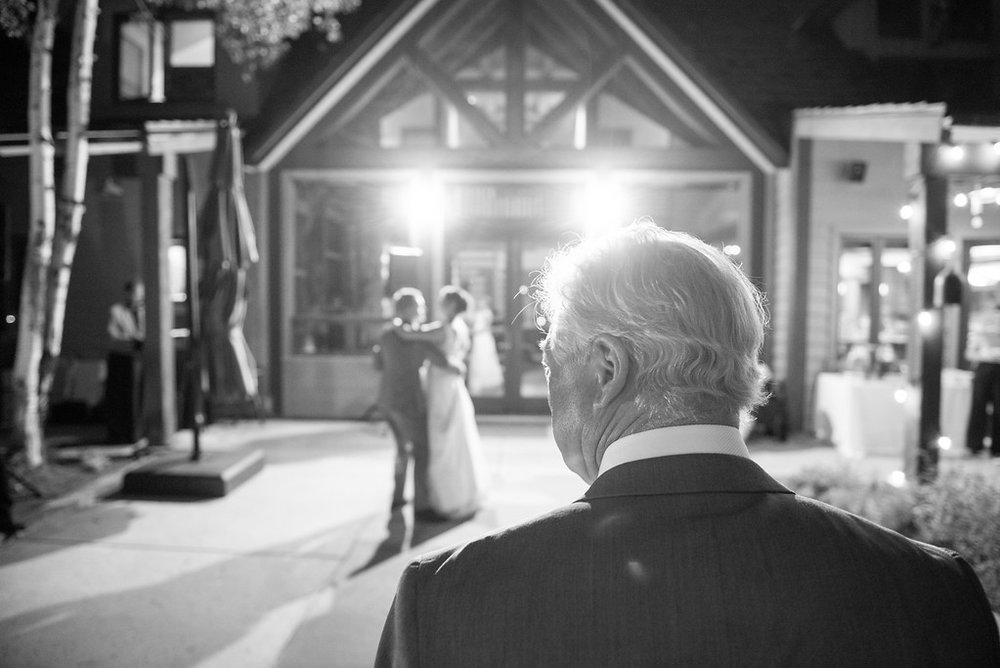 black and white photo of a father watching his daughter, the bride, dance with her groom in a backyard wedding