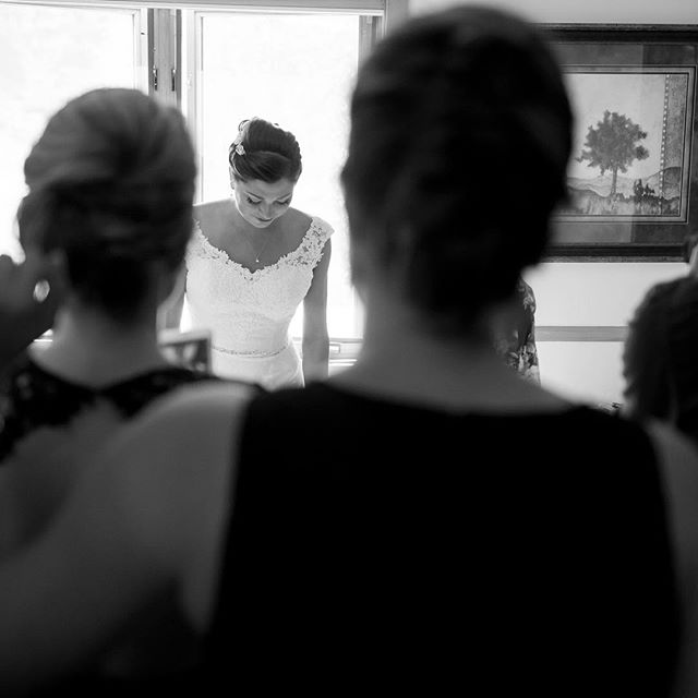 """The maid of honor just finished buttoning up the bride. I look to my left and realized that the shot was behind all of the brides maids watching this monumental moment. I quickly got behind them, the bride looked down at her dress in admiration, and """"click"""""""