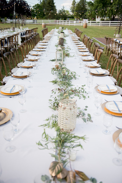 Stunning table spread for a rustic outdoor wedding with white and green colors