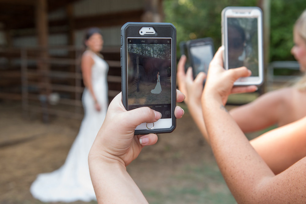 Wedding guests take photos of a bride on their iphones and androids at an outdoor wedding