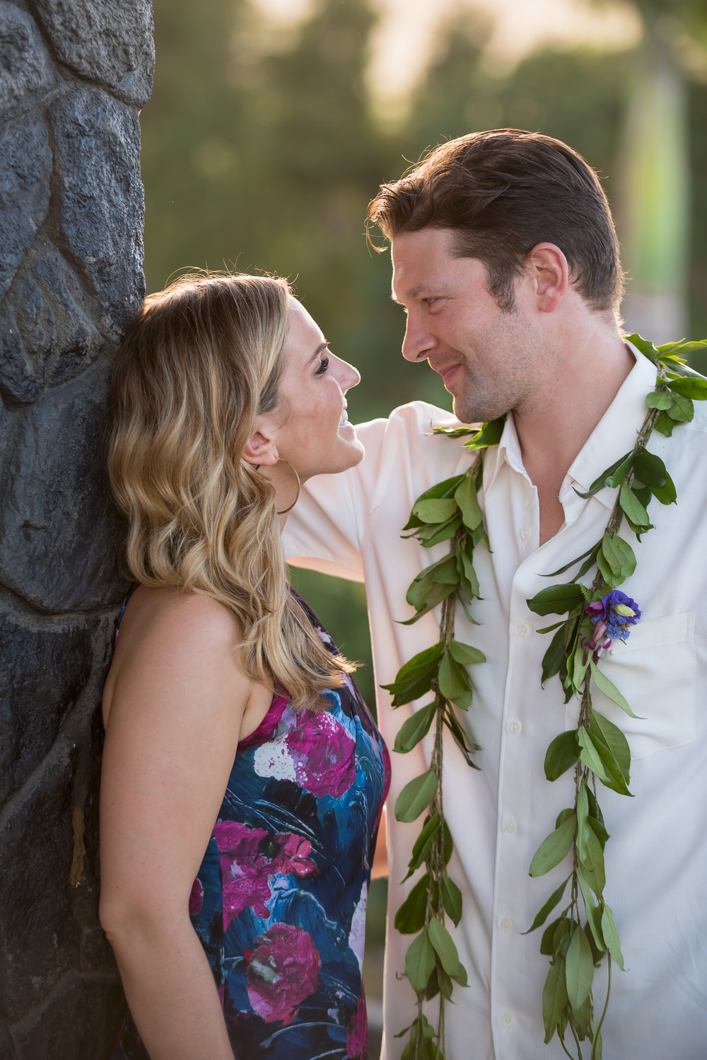 A couple smiles at each other during a resort sunset in hawaii, draped in lei and florals
