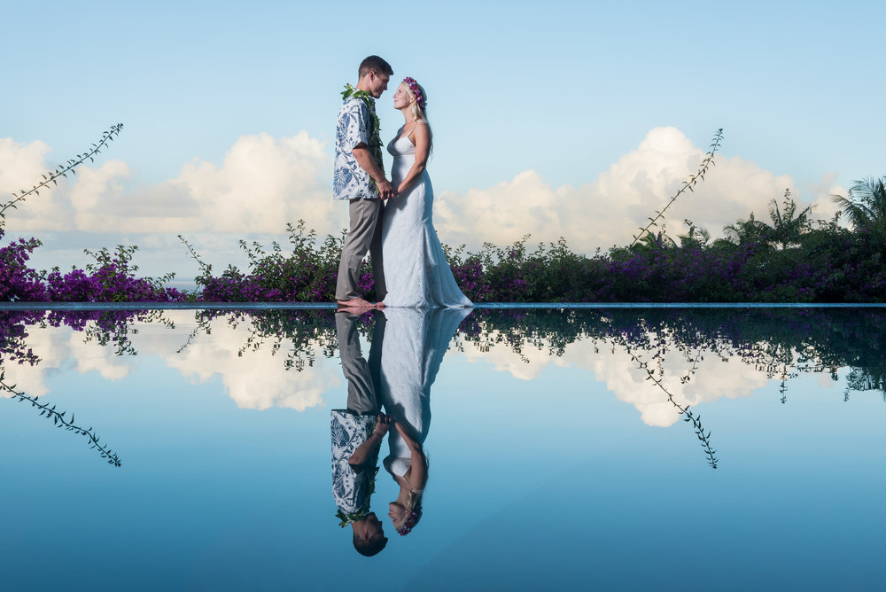 A bride and groom reflected in a tropical paradise