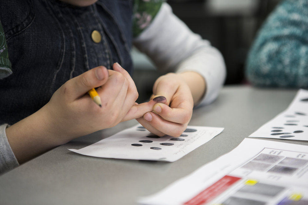 Emma DeCicco, 10, examines her own fingerprint during a forensic science workshop. Emma and the other participants learned fingerprint and handwriting analysis to solve a mystery of who stole the cookies.