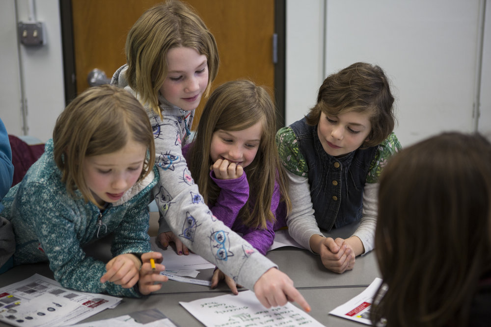 From left, Kora Purdy, Brianna Jecklin, Wren Wooten and Emma DeCicco analyze handwriting as part of a forensic science workshop held in conjunction with the UO Women in Graduate Science and the Eugene Science Center.
