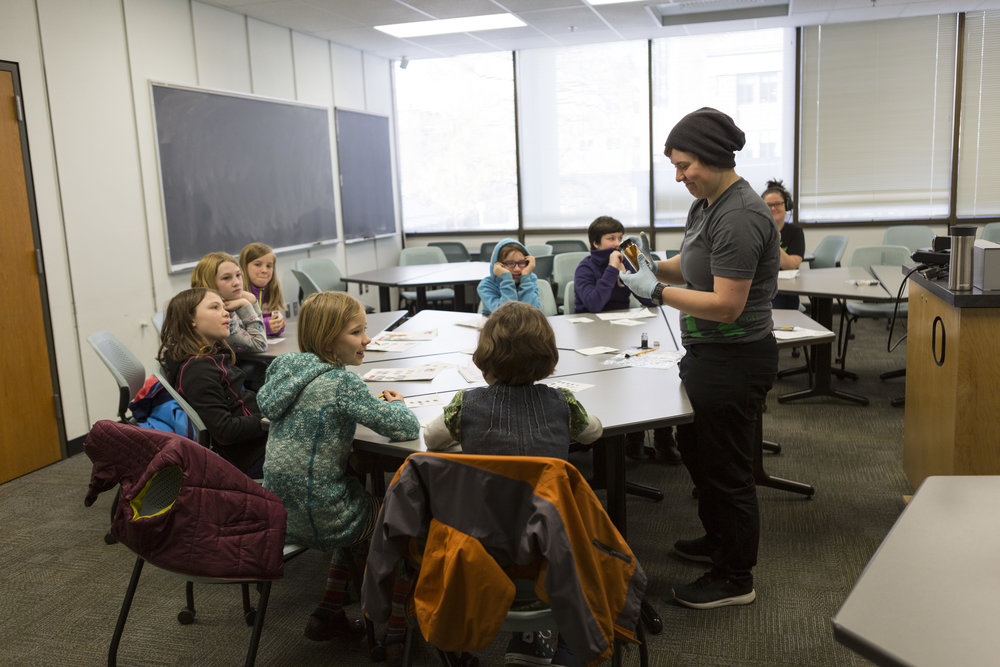 Lisa Eytel demonstrates fingerprinting techniques to young girls at a science workshop. Using learned fingerprint and handwriting analysis techniques the girls had to solve the mystery of who stole the cookies.
