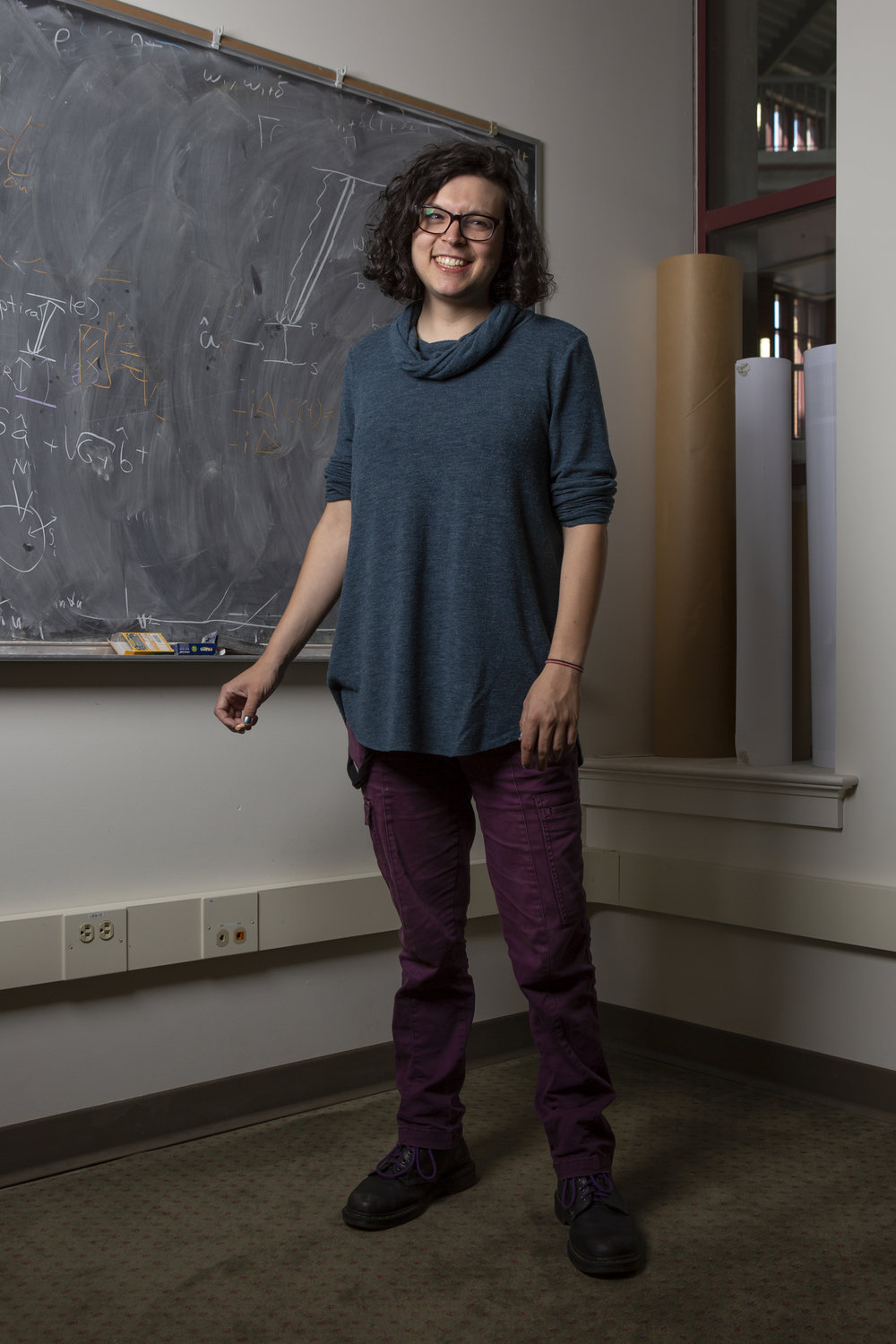 """Tzula Propp is a third-year physics Ph.D. candidate and member of LGBT in STEM. They identify as non-binary and gender-fluid. Though they feel supported by the physics department and their peers, they also struggle with a sense of belonging.  """"I'm too queer for my physics friends and too physics for my queer friends,"""" they said, """"I still get along with both of them, but it's a little bit of fitting in nowhere.""""  Propp studies quantum information theory. Specifically, they use the theories of quantum computing to understand the fundamental limits and tradeoffs of how well we can sense light."""