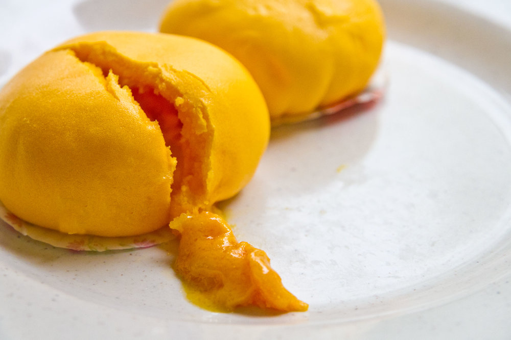 Liu Sha Bao  Take your time to burst into the Liu Sha bao and let the salted egg custard flow out in style. The bright yellow Liu Sha bao here attracts not only the taste but in sight.