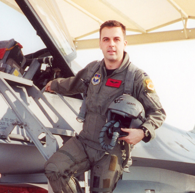 Maj. Troy Gilbert posed for a picture on the ladder of an F-16 at Luke Air Force Base in Arizona. Gilbert was the standardization and evaluation chief for the 332nd Expeditionary Operations Group and was deployed from the 309th Fighter Squadron out of Luke. Photo Credit: Air Force courtesy of Gilbert family