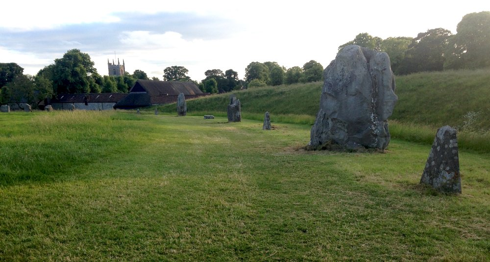 Avebury Stones with earth henge on the right and town in the middle background