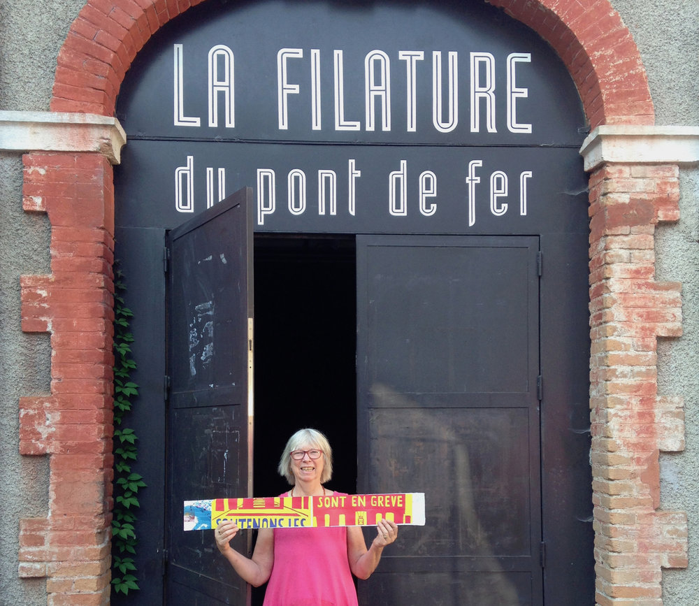 La Filature du Pont de Fer door ~ holding up a worker's rights poster from my woven artist book