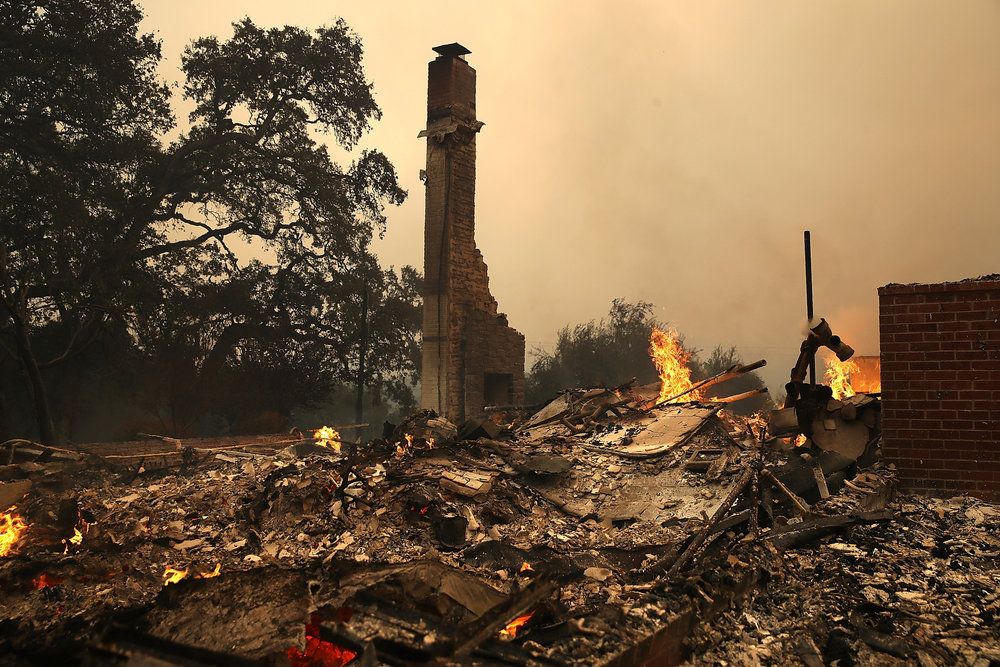 A firefighter hoses down a fire-ravaged home in Napa. (Marcio Jose Sanchez / Associated Press)