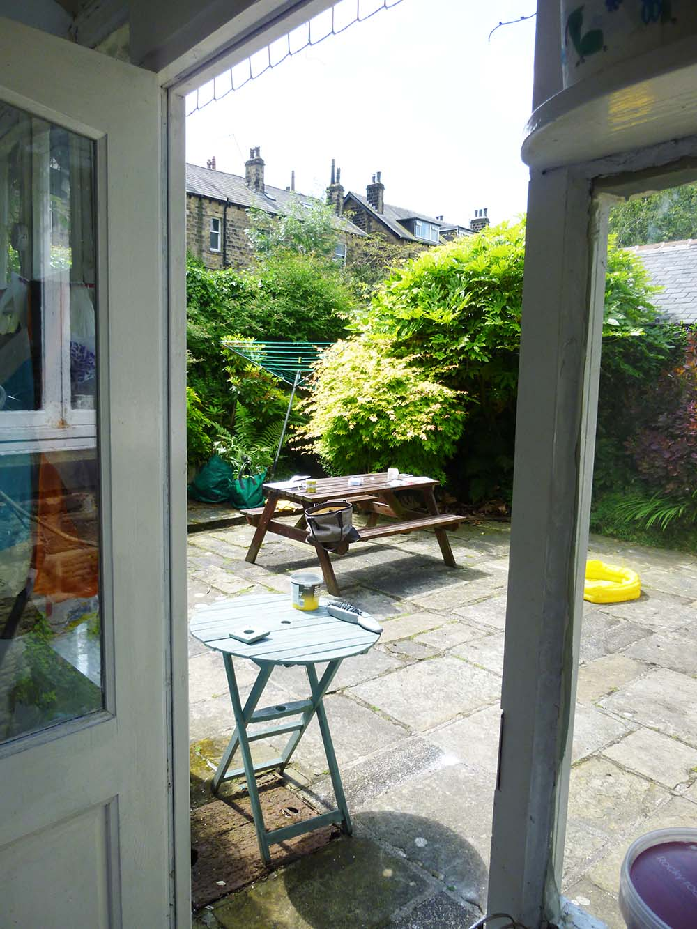 BEFORE:   View into the sunny flagged yard from the original back kitchen door.