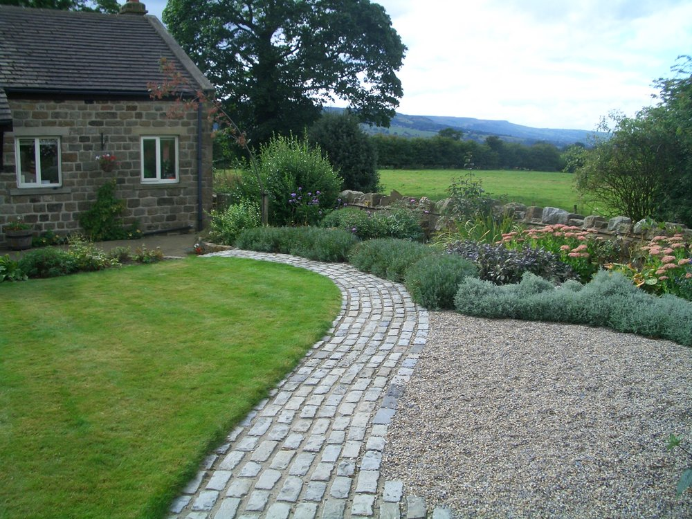 Reclaimed stone sett, curved path forms a pleasing approach to the house.