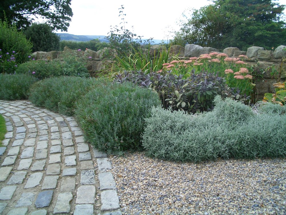 The colour of the reclaimed setts is echoed in the colour scheme of the planting.
