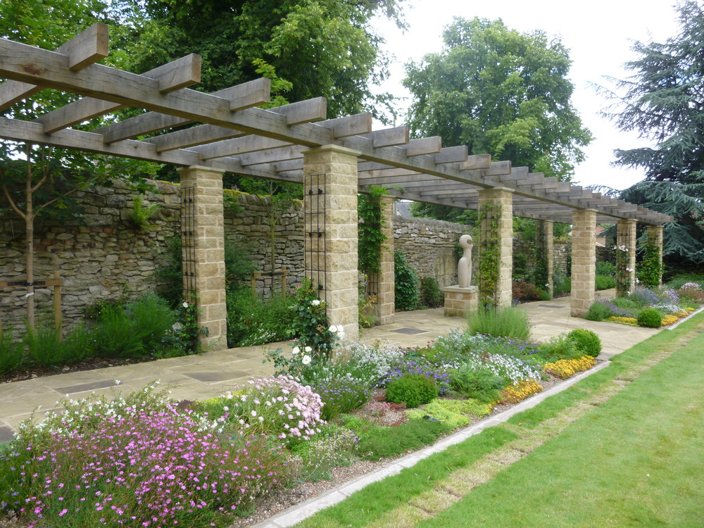 New pergola with stone piers and oak beams, metal supports for climbing roses.