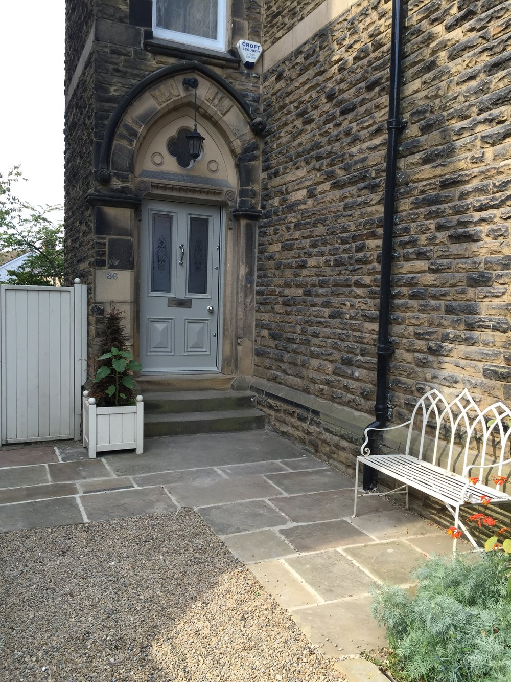 Reclaimed Yorkshire flags and seat at the house entrance.