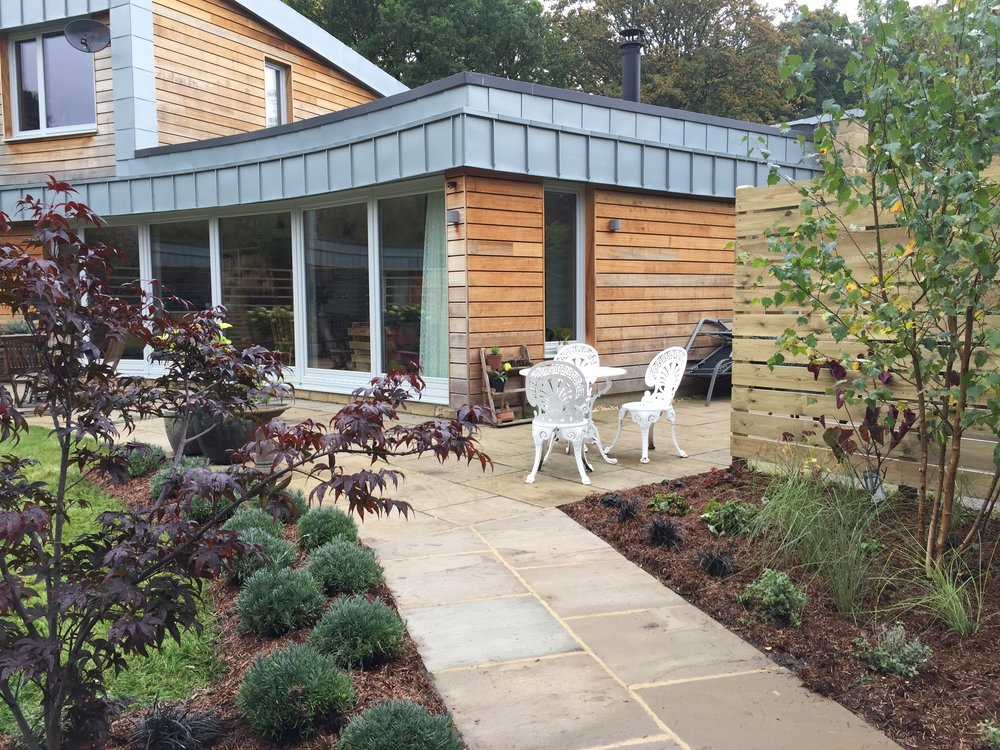 South facing sunny terrace edged with lavender. New planted borders and timber screen to bin store.