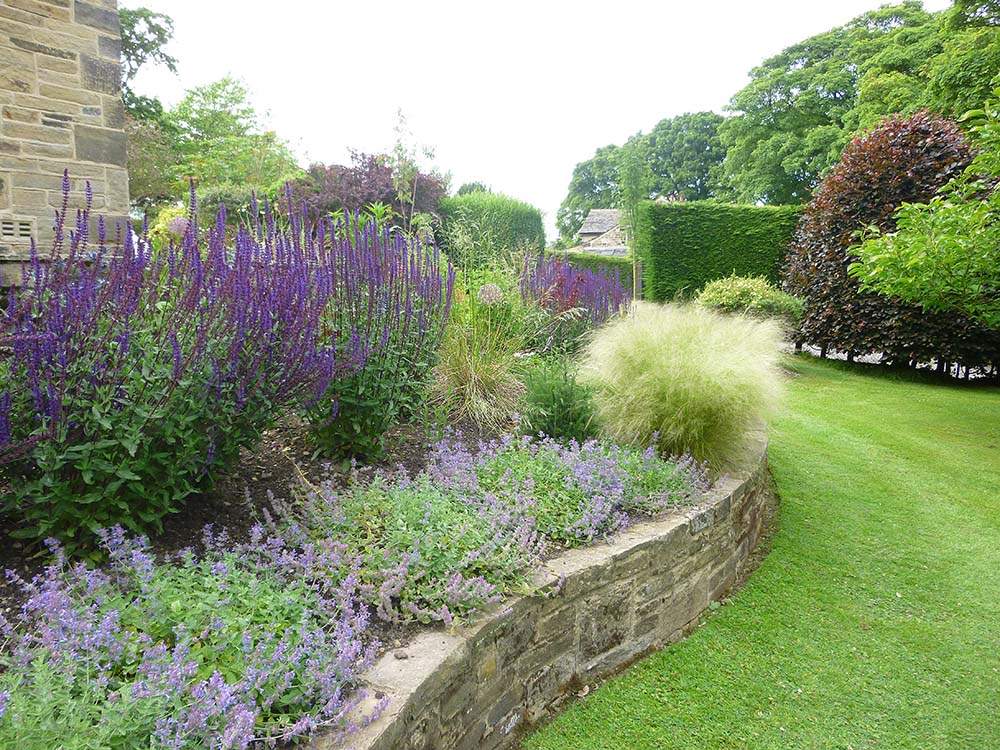 Large raised bed planted with swathes of perennials and grasses.
