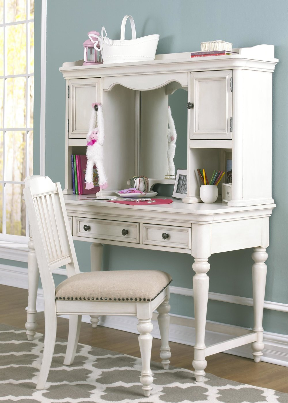 Everly Desk and Hutch - Multi-tasking is key in kids' rooms! The Everly Desk and Hutch features enough storage for books, pens, and more plus it has a mirror! Your young one can get ready for school in the mornings and complete their homework in the afternoons.The classic chair that matches features an upholstered seat and nailhead trim continuing the classic style.