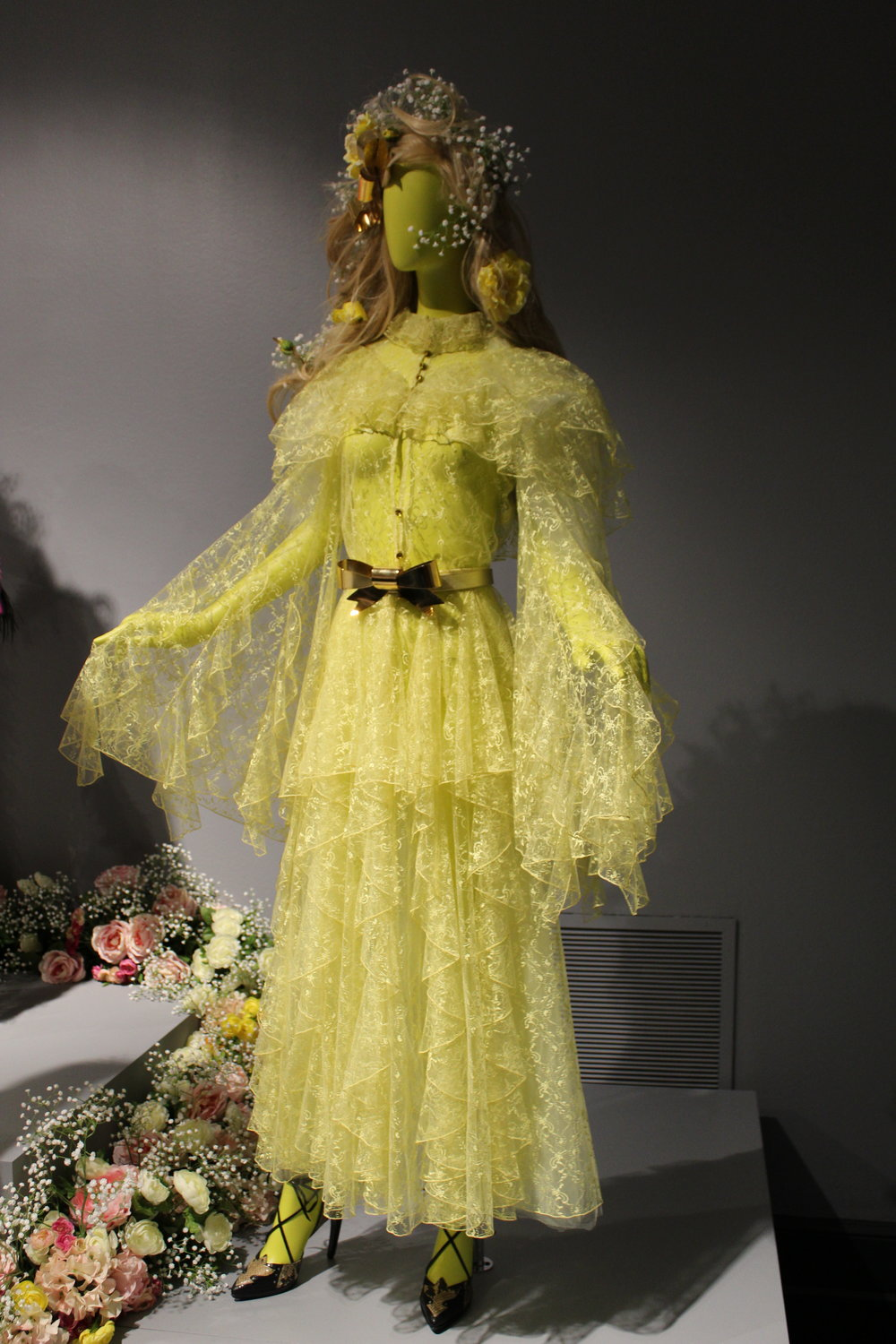 I enjoy the color itself, how the designers have paired solid yellow tights with the overall aesthetic of the dress, the ruffle layering of the fabric throughout the dress, along with the dramatic arms.