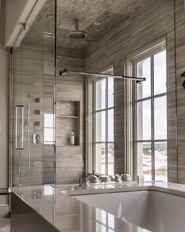 Built-in spa bathtub and custom glass shower designed with silver travertine tiles. #achristopherhome