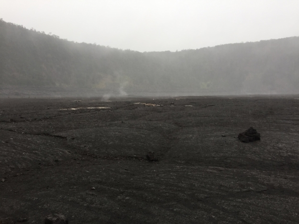 Steam rising from the crater's surface cracks.