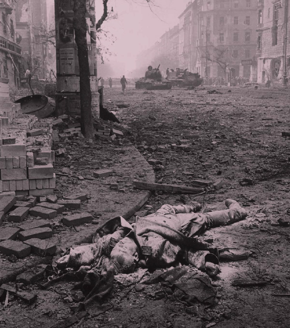 A dead Russian soldier in the streets of Budapest with Russian  tanks rolling in the background during the Hungarian Uprising in late October 1956.
