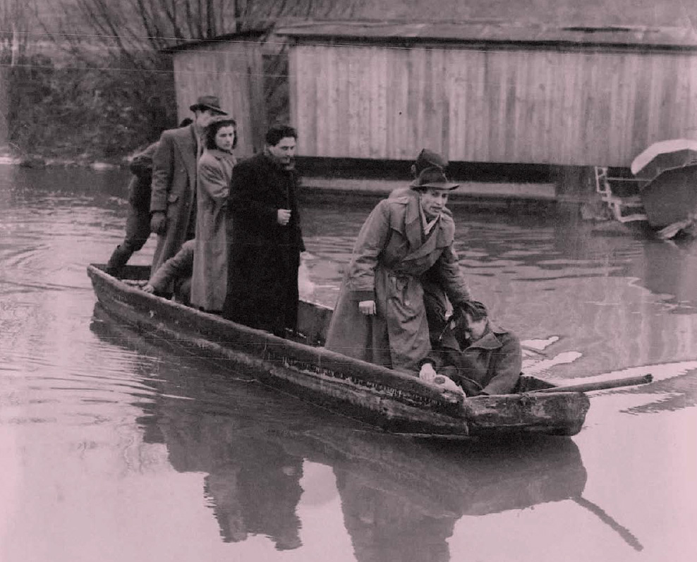 Hungarian Refugees cross a canal in a boat on November 21, 1956, on the way to Austria; the man in front is totally exhausted.