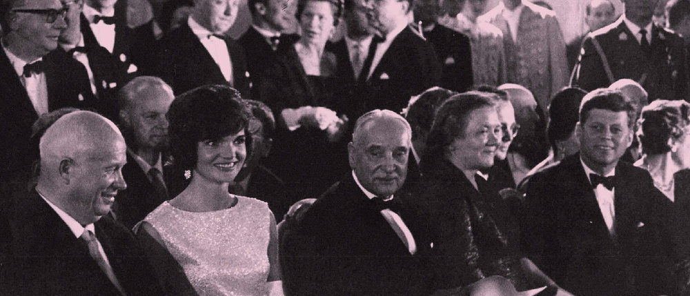 "In the evening of June 3, 1961, Austrian President Adolf Schärf gives a gala dinner at Schönbrunn Palace, for the American and Soviet delegations to the Vienna Summit. After dinner the ballet of the Vienna State Opera danced the Strauss Waltz ""On the Beautiful Blue Danube."" Chairman Khrushchev, First Lady Jacqueline Kennedy, President Schärf, Soviet First Lady Nina Khrushcheva, and President Kennedy (from left to right), with diplomatic delegations in the background."