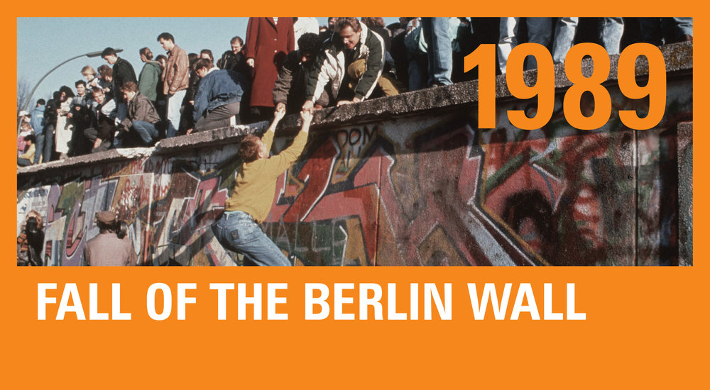 Giddy Germans climb the Berlin Wall after its opening on November 9.