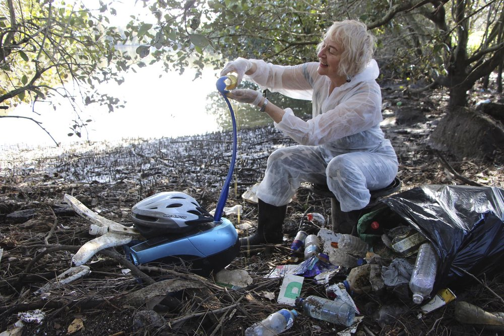 2054 - A citizen feeds her pet Flinger in the plastics garden on the Cooks River mangroves,  Sydney.