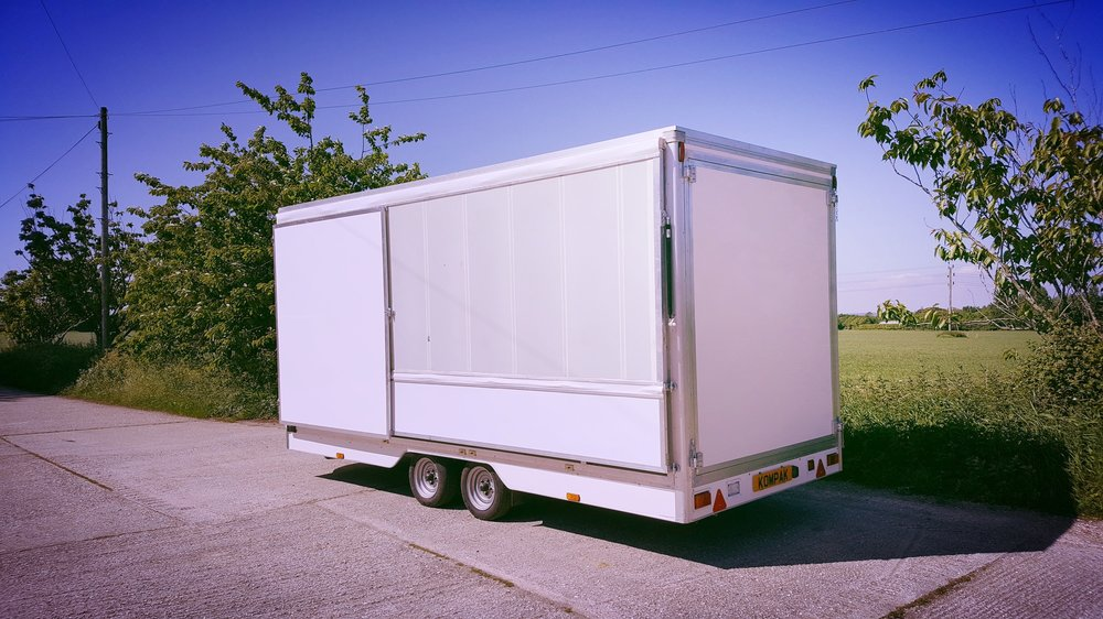 Branded promotional exhibition trailer for events and expo with canopy and fold out doors, easy access ramp and headboard, logo, manufactured in Sussex by Blackburn Trailers