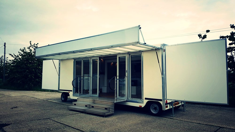 Branded promotional exhibition trailer for events and expo with canopy and fold out doors, fully glazed front, easy access ramp and headboard, logo, manufactured in Sussex by Blackburn Trailers