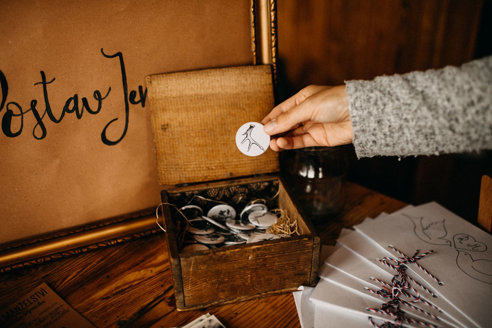 bride holding a pin with their wedding symbols