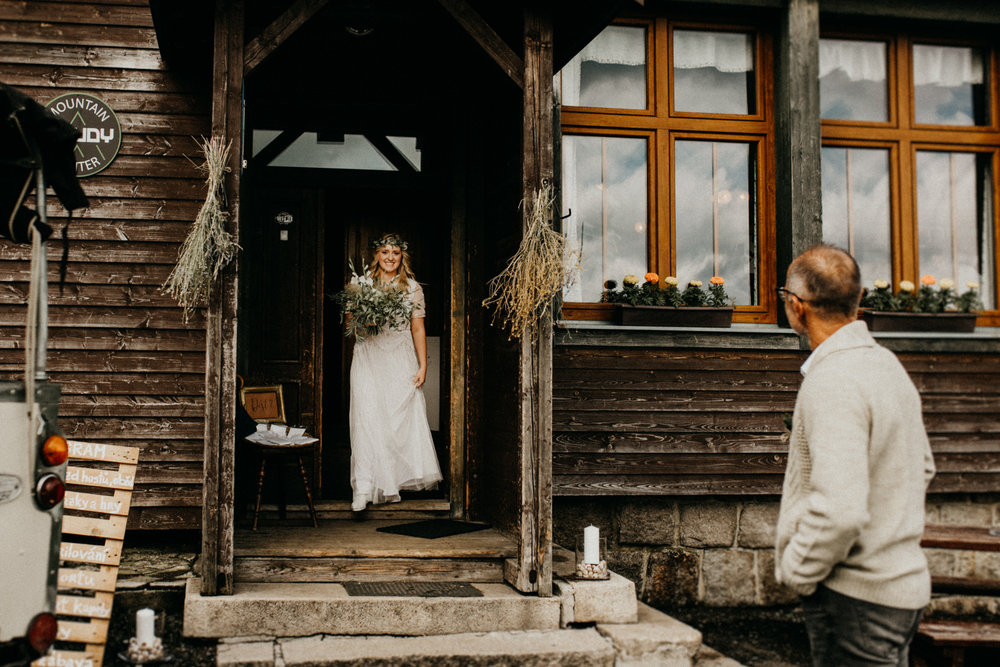 first look between the bride and her father in front of a the cabin