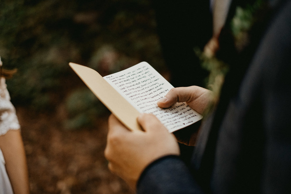 groom reading his vows in the forest