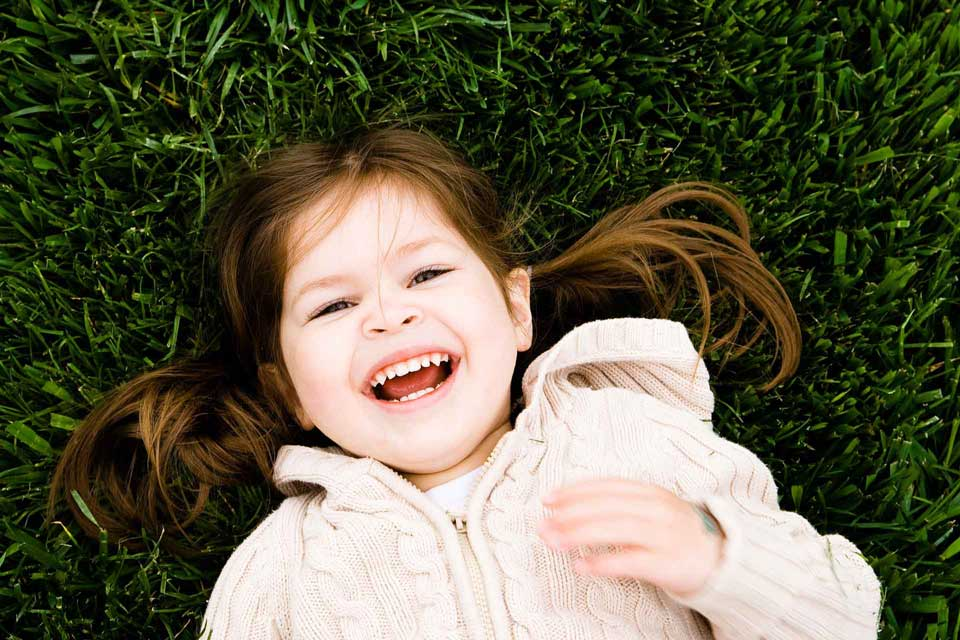 little-girl-laying-in-the-grass-smiling-at-the-camera.jpg