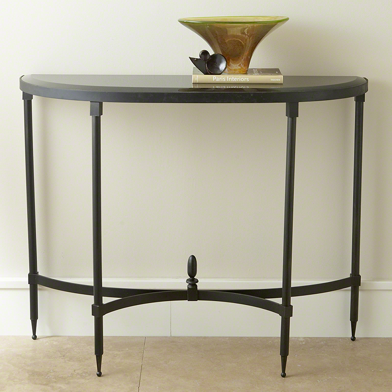Fluted Console Table - The legs are fluted iron with bowed cross stretchers and an oblong oval finial. The top is black granite in a demi Lune shape. Size 42″W x 33.25″H x 13.75″Deep