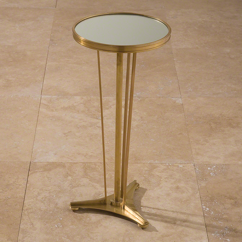 French Cocktail Table - French Moderne Side Table-Antique Brass & Mirror.  Streamlined and elegant, our French Moderne Side Table gives your space the luxe look you need without the fuss you don't. The cast brass table sits on a three legged base and is topped with a mirrored surface. 12