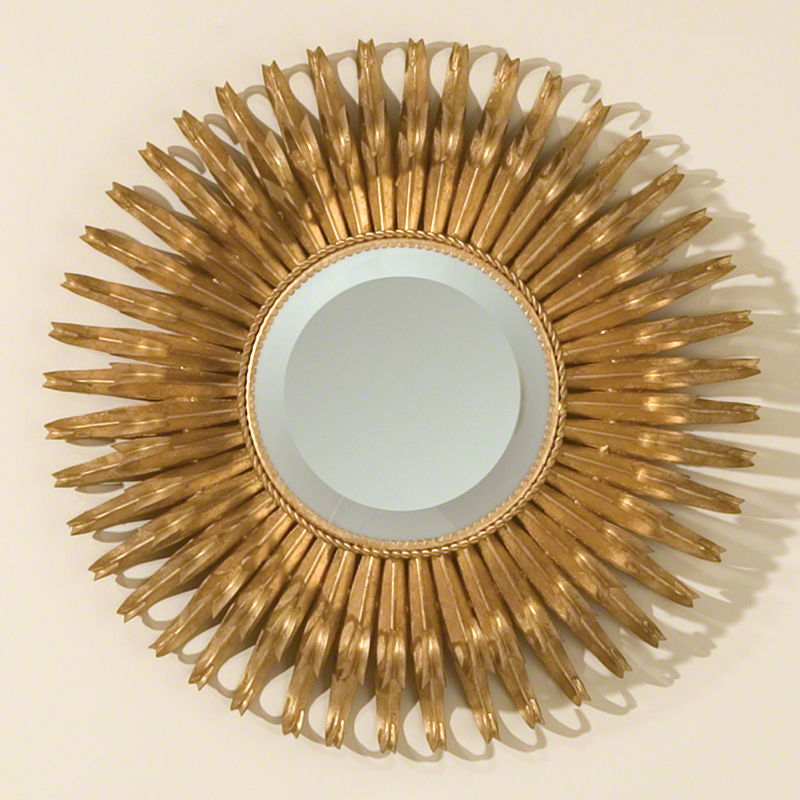 Sunburst Mini-mirror - Organic leaf shapes in a perfect circle form our Round Gold Leaf Sunburst Mirror. The center holds a bevelled mirror that contrasts beautifully with the warm and glowing gold leaf finish of the leaves.  20