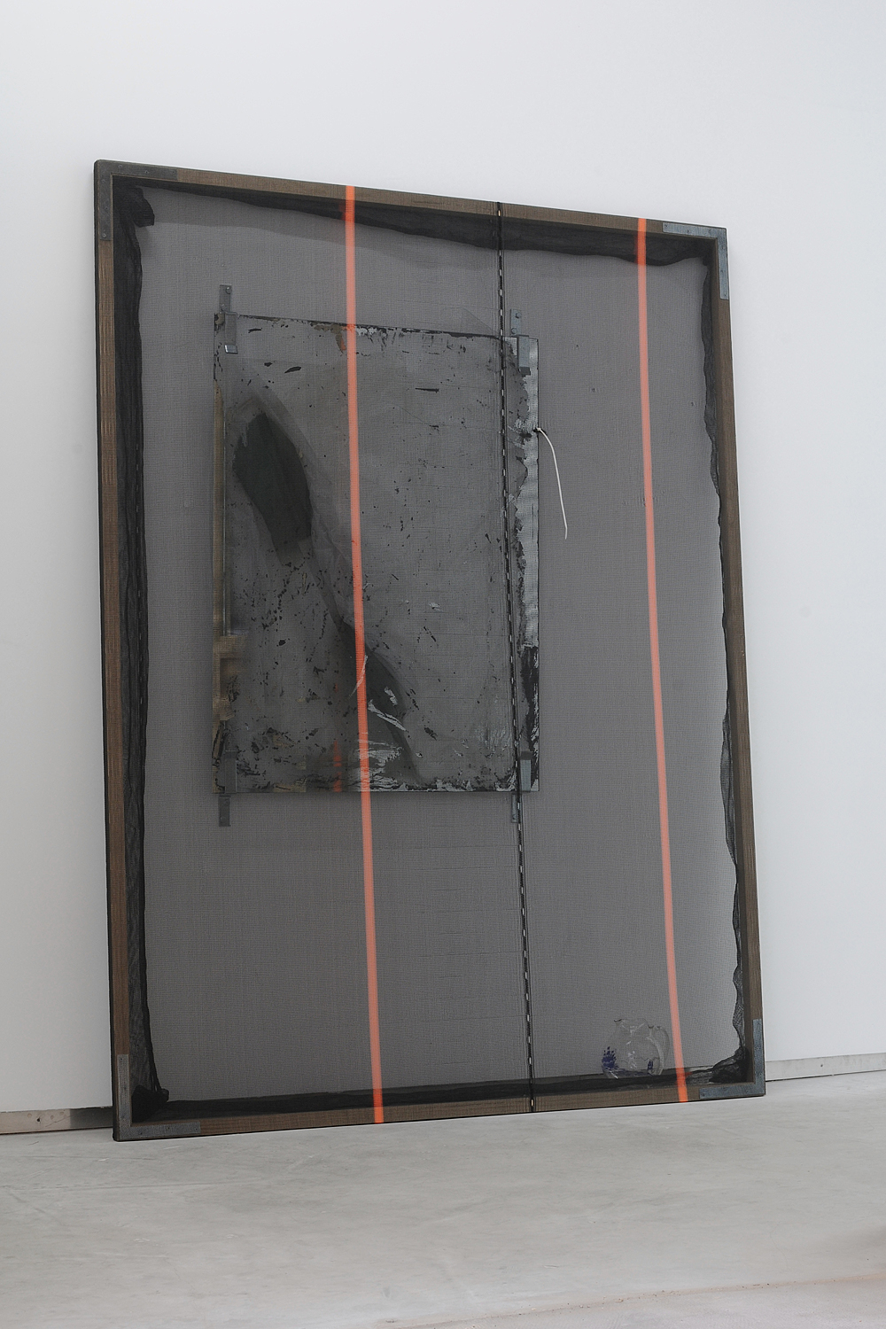 Valerie Snobeck,  New Construct,  2011, debris netting, partially removed mirror, peeled prints on plastic, depression glass, door barricade brackets, wood frame, gesso, hardware, 243,9 x 182,9 cm